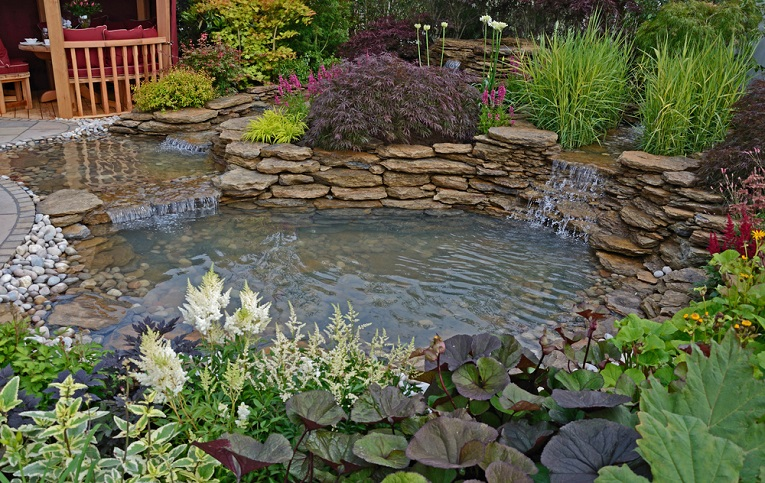 The pond area and terrace with Summer House in an aquatic garden